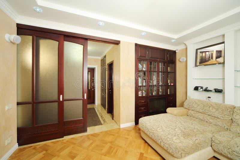 Hyra rum med soffan, träbokhylla med spisen royaltyfria foton