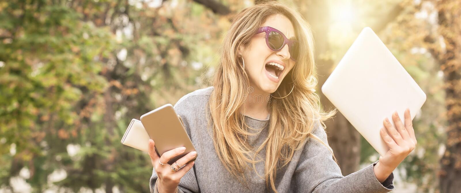 Hysterical girl with too many screens, mobils, tablets and laptops stock image
