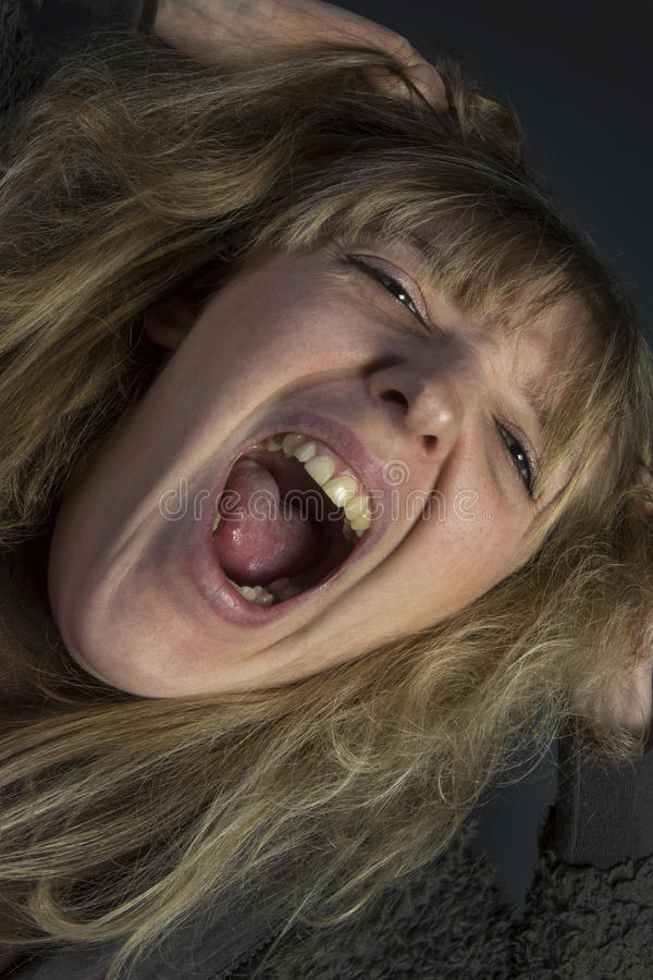 Hysterical Woman. An hysterical screaming young woman royalty free stock images