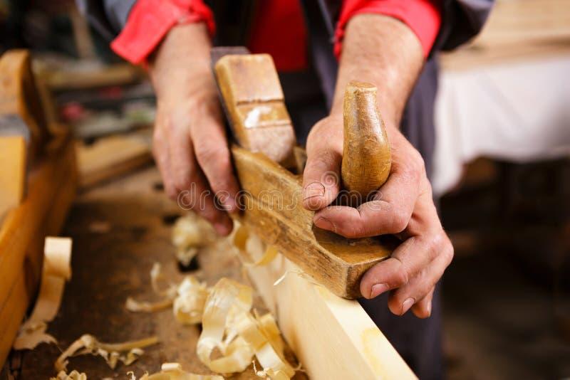 Hyvlare på arbete i ojämna manliga händer royaltyfria bilder