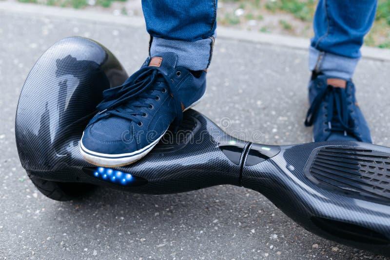 Iść na piechotę mężczyzna stoi na błękitnej platformie w sneakers i cajgach Zaczyna używać hulajnoga, hoverboard lub gyroscooter  zdjęcie royalty free