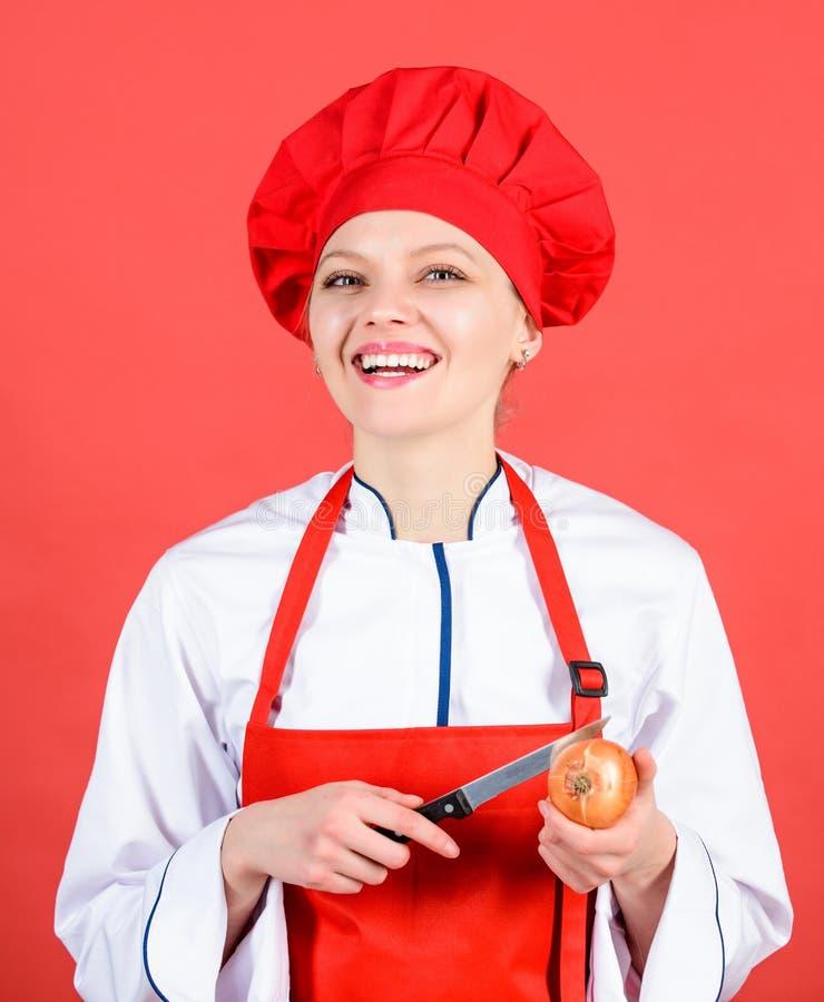 i Νοικοκυρά με το μαγείρεμα του μαχαιριού και του κρεμμυδιού επαγγελματικός αρχιμάγειρας στην κουζίνα στοκ εικόνα