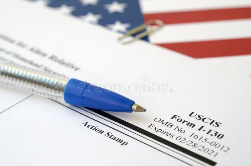 I-130申请外国人相对空白形式的请愿书悬挂在美国国土安全部的蓝笔国旗上 免版税库存图片