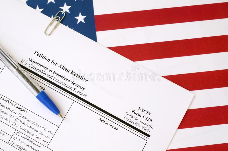 I-130申请外国人相对空白形式的请愿书悬挂在美国国土安全部的蓝笔国旗上 免版税库存照片