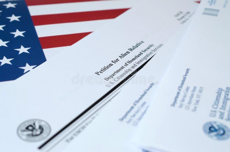 I-130申请外国人相对空白形式的请愿书悬挂在美国国旗上,上面有国土安全部的信封 免版税库存图片