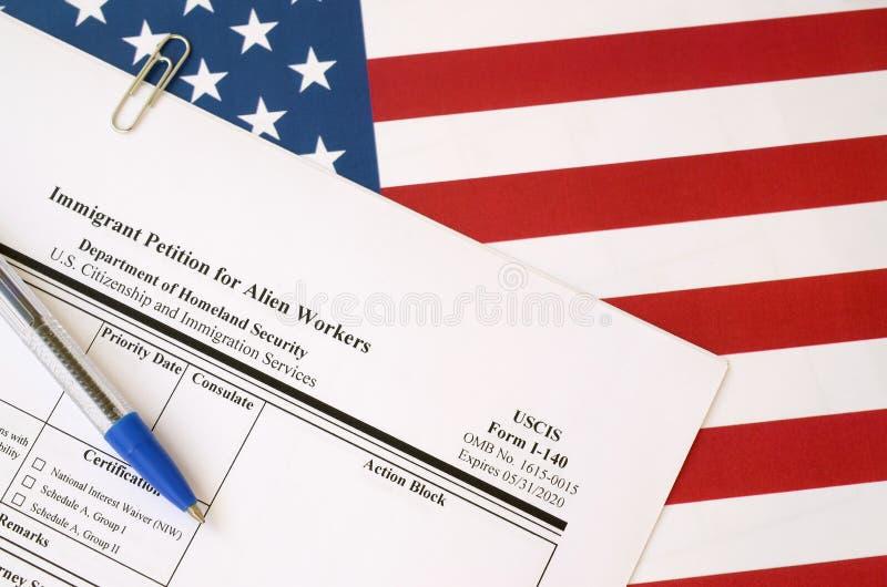I-140移民申请外国工人空白表格,贴在美国国土部的蓝笔旗帜上 免版税库存照片
