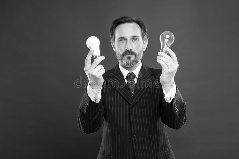 ?i?? 能源节约 在企业成套装备的男性 有灯的成熟有胡子的人 在衣服举行电灯泡的商人 免版税库存照片