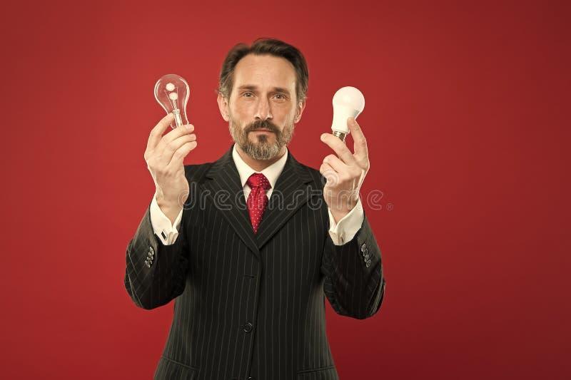?i?? 能源节约 在企业成套装备的男性 有灯的成熟有胡子的人 在衣服举行电灯泡的商人 免版税库存图片