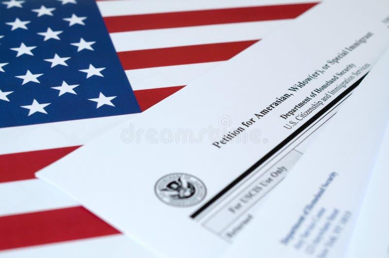 I-360申请美洲人、鳏夫或特殊移民空白形式的请愿书悬挂在美国国旗上,上面有来自美国国务院的信封 库存图片