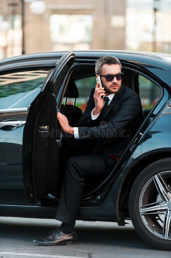 I am already here. Confident young businessman talking on the mobile phone while coming out of his car stock photos