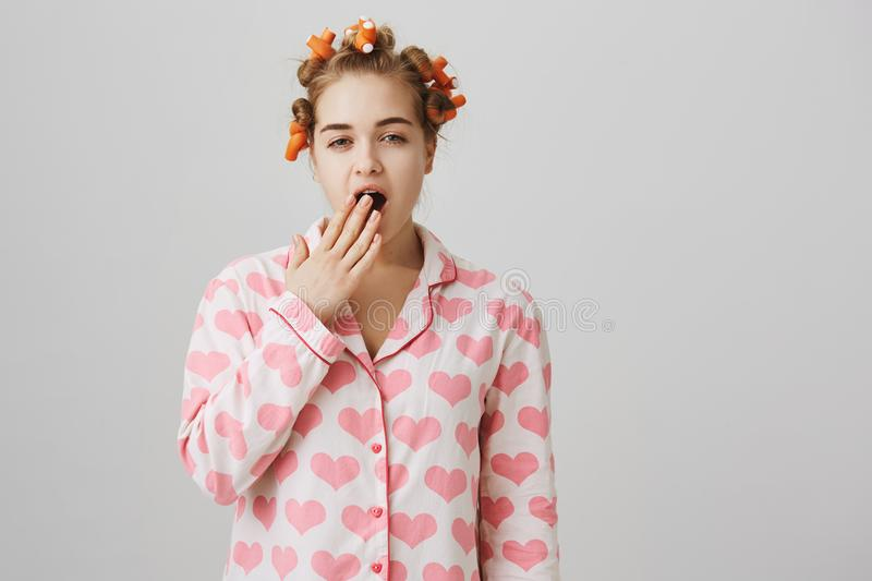 Am I already pretty. Portrait of funny cute caucasian girl at home, wearing hair curlers, trying to create beautiful stock images