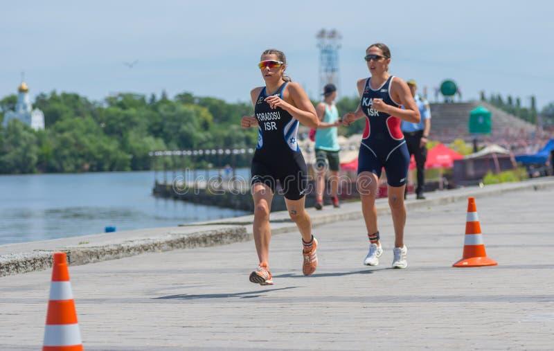 I andra hand Raz Poradosu och tredje ställe Shira Katz som konkurrerar på loppet för kvinna` s under den Dnipro ETU triathlonen J royaltyfri bild