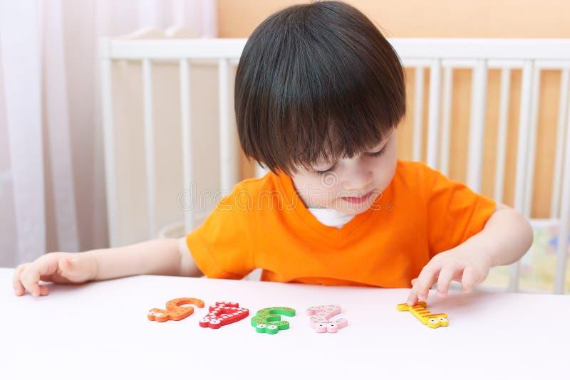 I 2 anni adorabili di bambino impara contare Gioco educativo fotografia stock