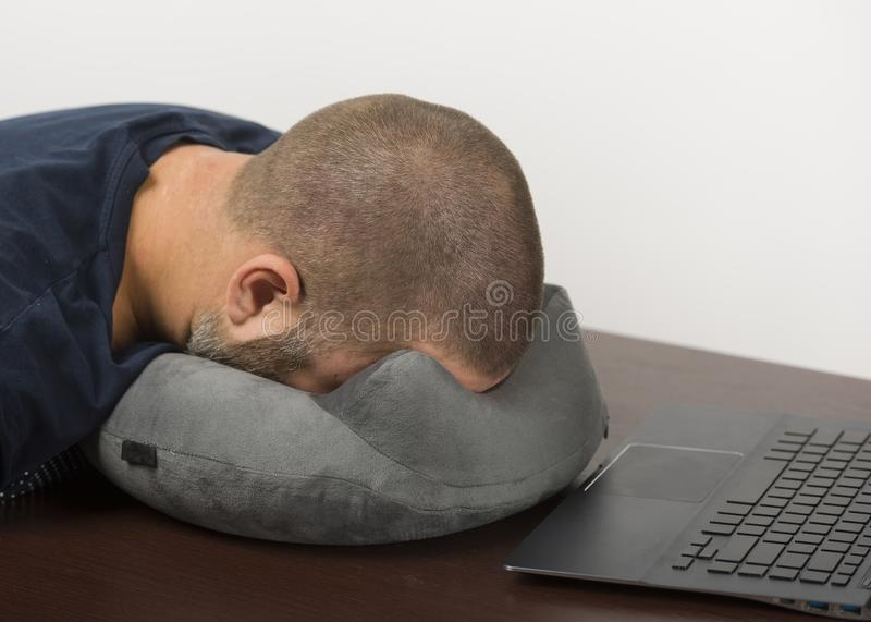 I 30 anni stanchi di bugie dell'uomo affrontano giù sul cuscino Concetto della morte da lavoro eccessivo fotografia stock