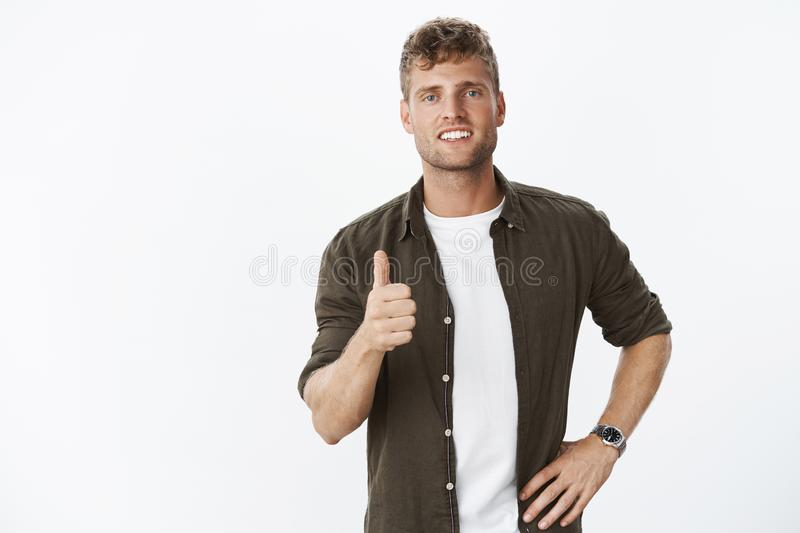 I approve. Portrait of satisfied good-looking charismatic european man with blue eyes, mascules and fair hair. Showing thumbs up and grinning pleased with good royalty free stock photos