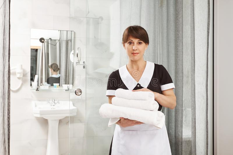 I assure you will have great time in our hotel. Portrait of pleasant caucasian woman working as housemaid, holding stock photography