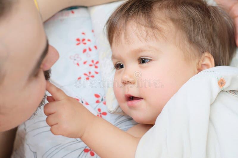 I baffi del papà commovente della piccola neonata immagini stock