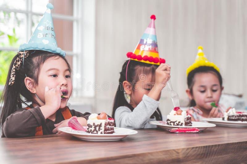 I bambini è felici mangiando la sua torta di compleanno nel partito fotografie stock libere da diritti