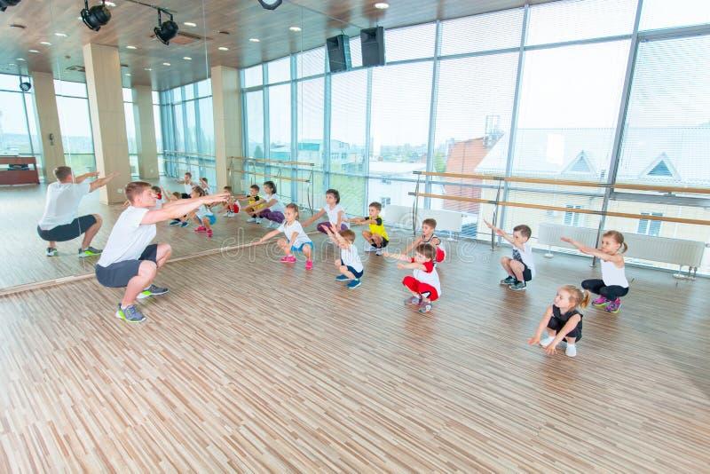I bambini alla lezione di educazione fisica nella ginnasta della palestra della scuola scherzano fotografia stock