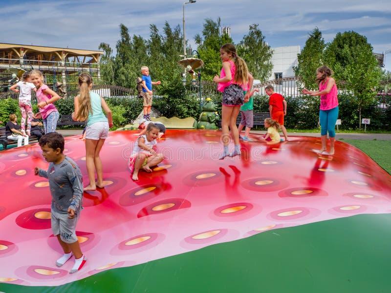 I bambini allegri non identificati stanno saltando il divertimento sul trampolino gonfiabile immagine stock