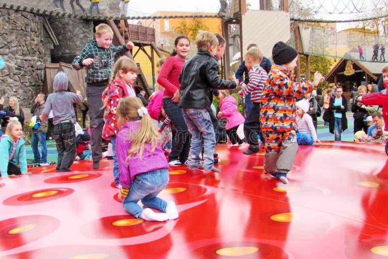 I bambini allegri stanno saltando il divertimento su un trampolino gonfiabile rosso fotografia stock