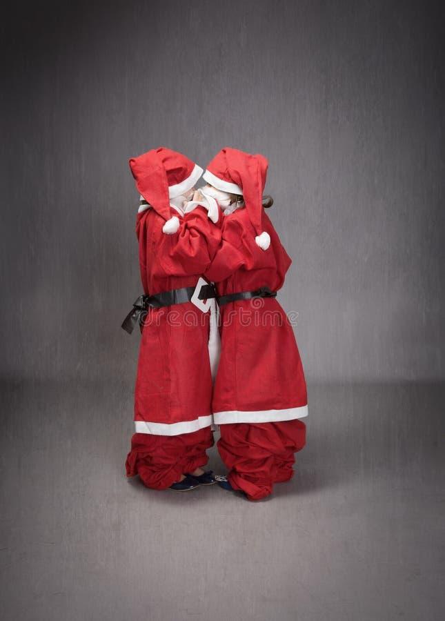 I bambini anonimi gradiscono il piccolo assistente del Babbo Natale immagine stock
