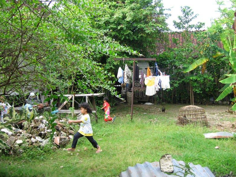 I bambini asiatici gioca il nascondino sul cortile immagini stock