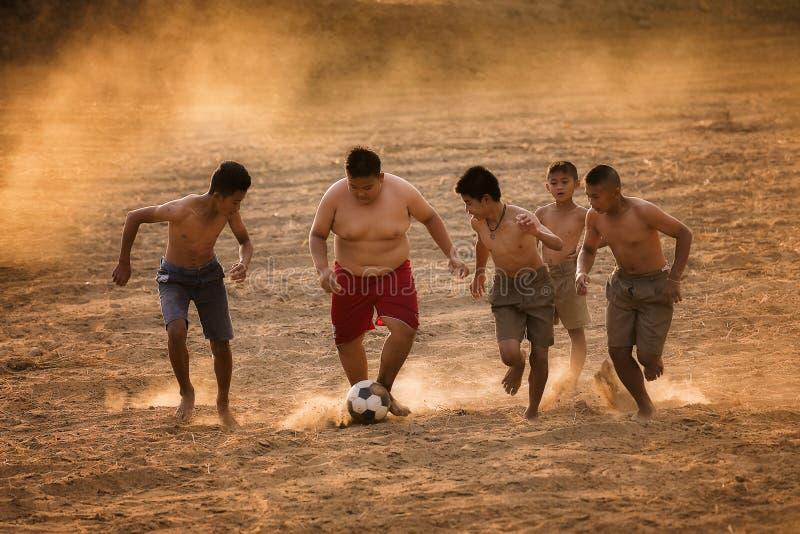 I bambini asiatici giocano a calcio immagine stock