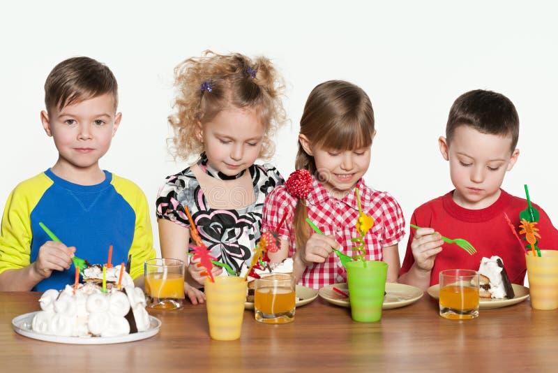 I bambini celebrano il compleanno alla tavola fotografia stock