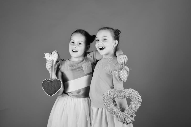 I bambini celebrano il giorno di biglietti di S. Valentino Sorelle con i cuori simili a pelliccia e molli fotografia stock libera da diritti