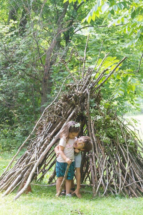 I bambini che giocano accanto al bastone di legno alloggiano assomigliare alla capanna indiana, immagini stock libere da diritti