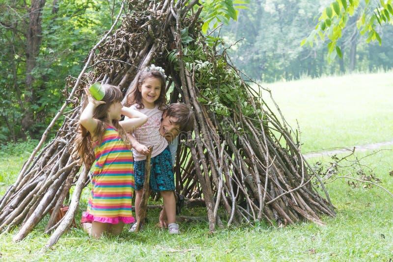 I bambini che giocano accanto al bastone di legno alloggiano assomigliare alla capanna indiana, immagine stock libera da diritti