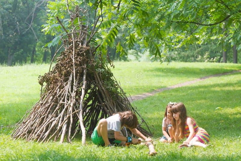I bambini che giocano accanto al bastone di legno alloggiano assomigliare alla capanna indiana, fotografia stock libera da diritti