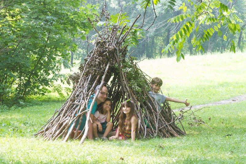 I bambini che giocano accanto al bastone di legno alloggiano assomigliare alla capanna indiana, immagine stock