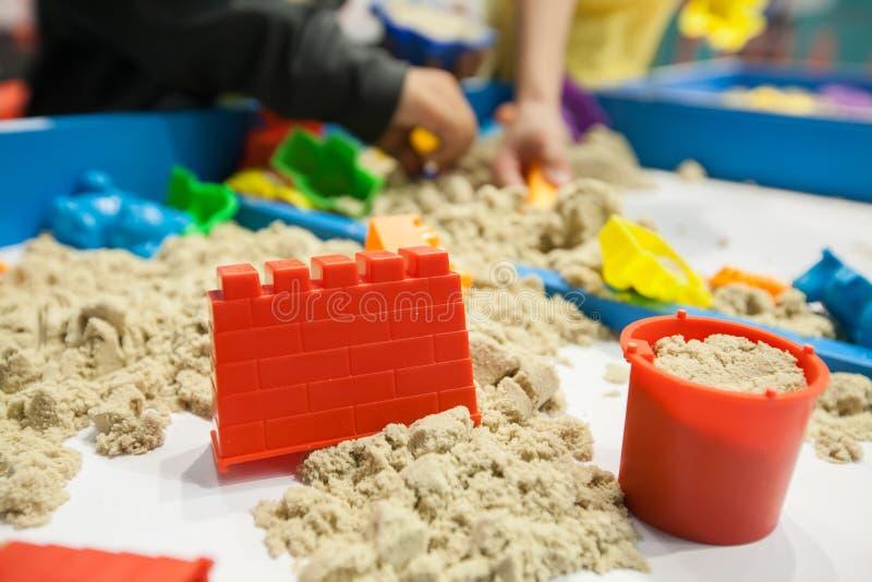 I bambini che giocano la muffa di plastica gioca con la sabbia sulla sabbiera fotografie stock