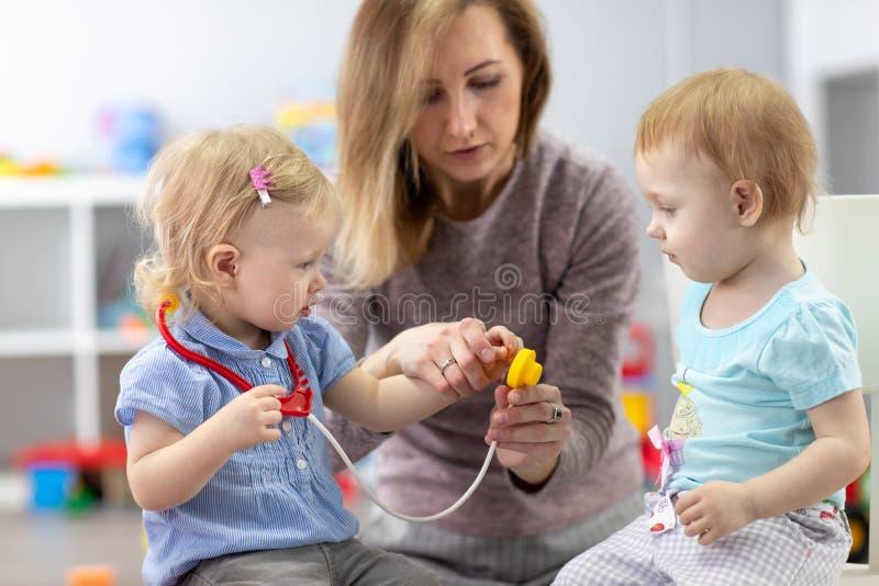 I bambini che imparano con un insegnante sono un medico e un paziente fotografia stock libera da diritti