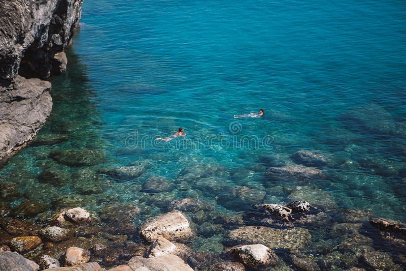 I bambini che nuotano nell'oceano innaffiano sotto in Cinque Terre Italy fotografia stock
