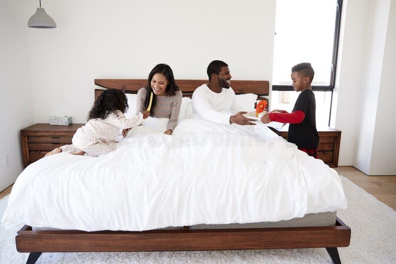 I bambini che portano i genitori fanno colazione a letto per celebrare il giorno o il compleanno di padri del giorno di madri immagini stock