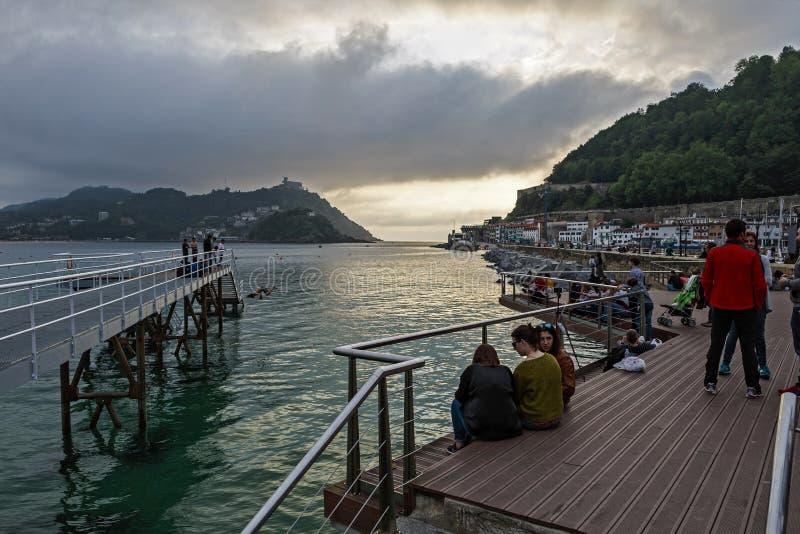I bambini che saltano in Concha della La abbaiano al tramonto in San Sebastian fotografia stock