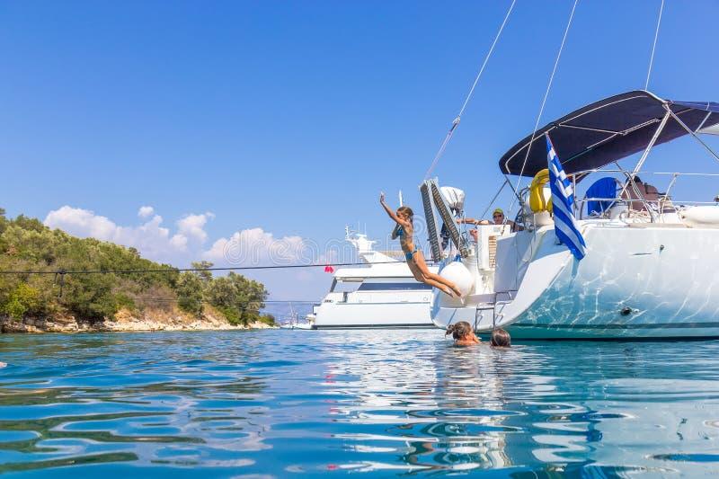 I bambini che saltano dalla barca a vela immagine stock