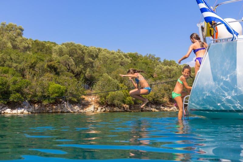 I bambini che saltano dalla barca a vela fotografia stock libera da diritti