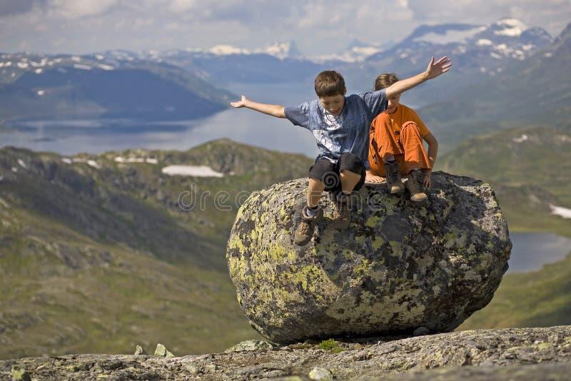 I bambini che saltano dalla grande pietra fotografia stock libera da diritti