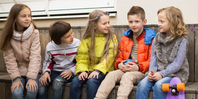 I bambini comunicano la seduta sul banco nell'iarda fotografia stock
