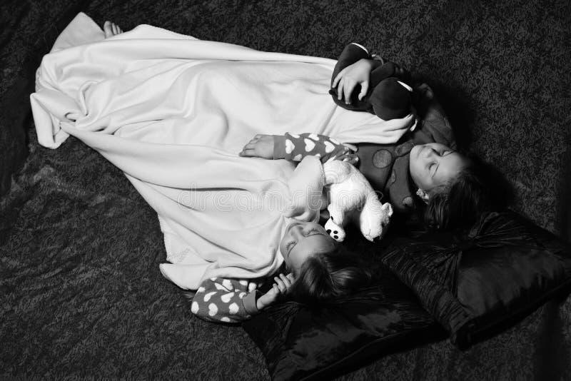 I bambini con i fronti pacifici si trovano sotto la coperta sul letto Concetto di felicità e di infanzia Ragazze nel sonno dei pi fotografia stock libera da diritti