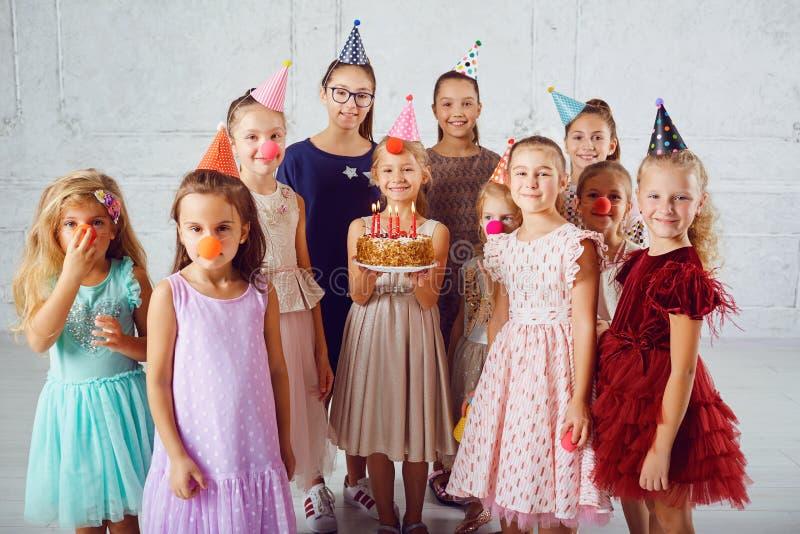 I bambini con una torta di compleanno si divertono immagini stock