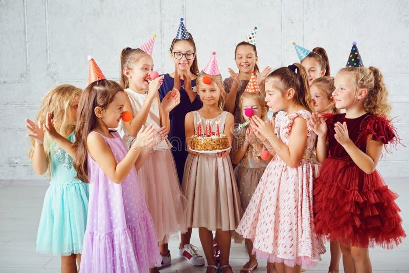 I bambini con una torta di compleanno si divertono immagine stock