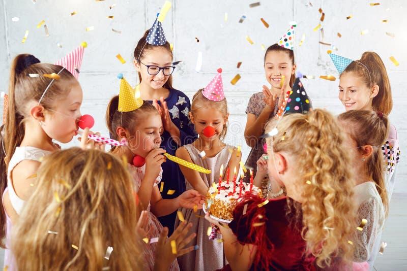 I bambini con una torta di compleanno si divertono fotografia stock