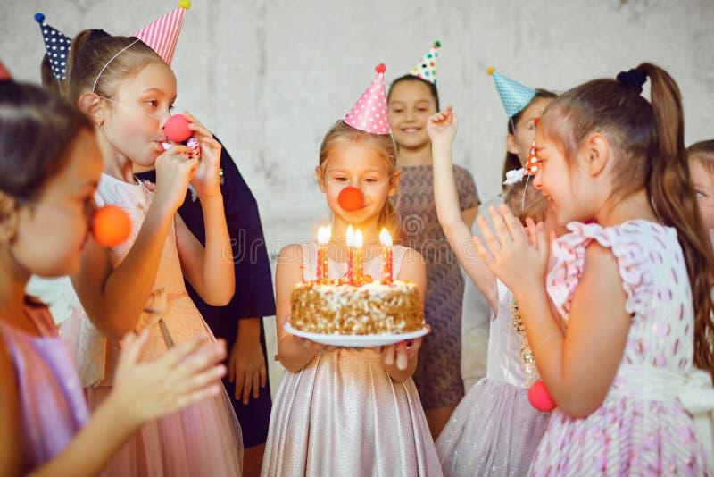 I bambini con una torta di compleanno si divertono fotografie stock libere da diritti
