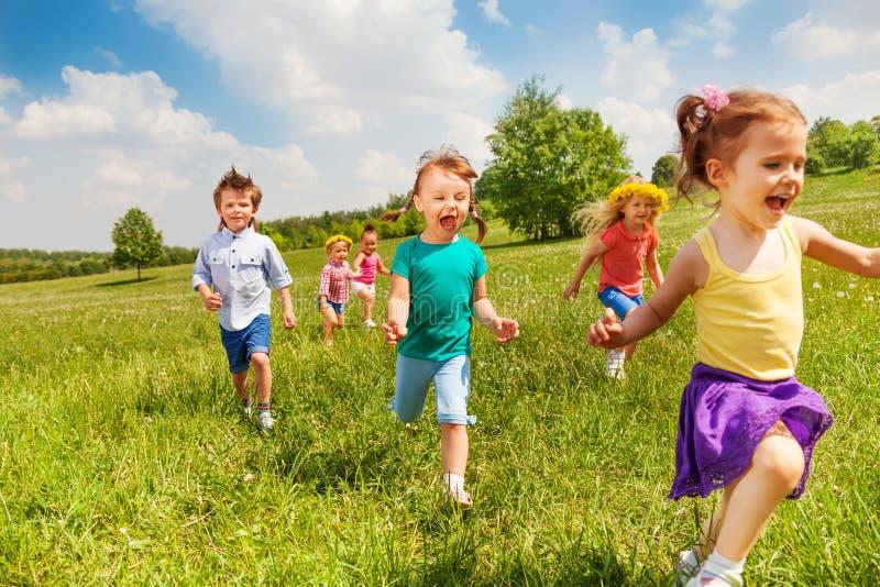 I bambini correnti emozionanti nel campo verde giocano insieme fotografia stock libera da diritti