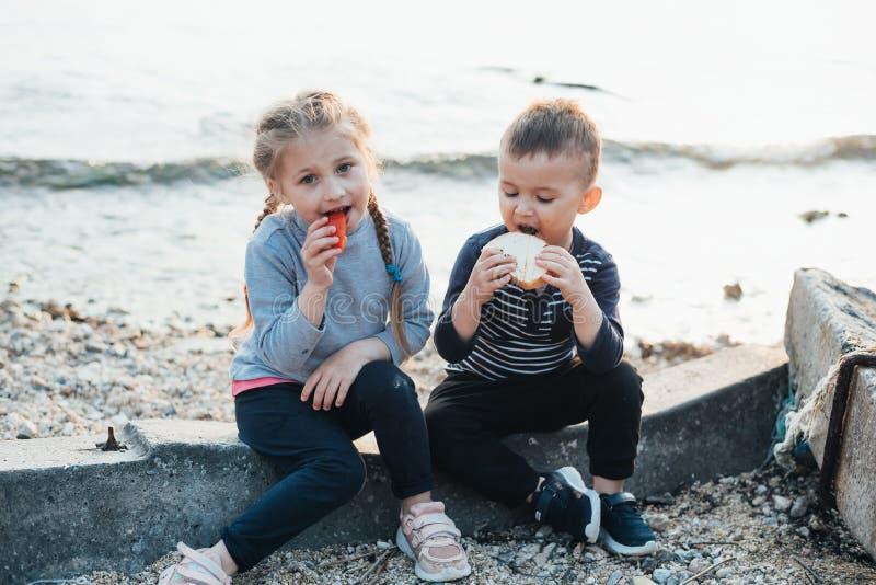 I bambini del mare mangiano il pane della ragazza e del ragazzo del pomodoro tostato fotografie stock libere da diritti